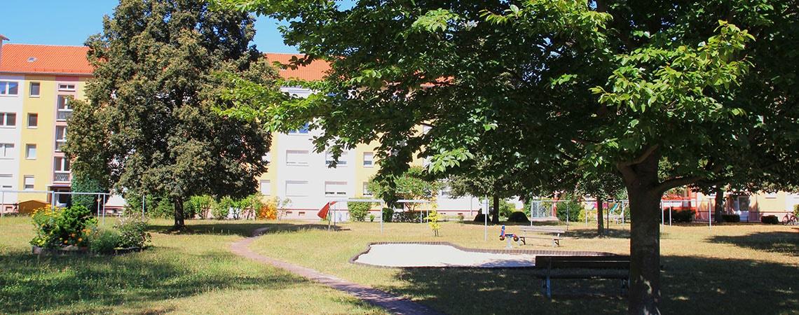 Häuser Fassade eines Mehrfamilienhauses mit einem Spielplatz davor